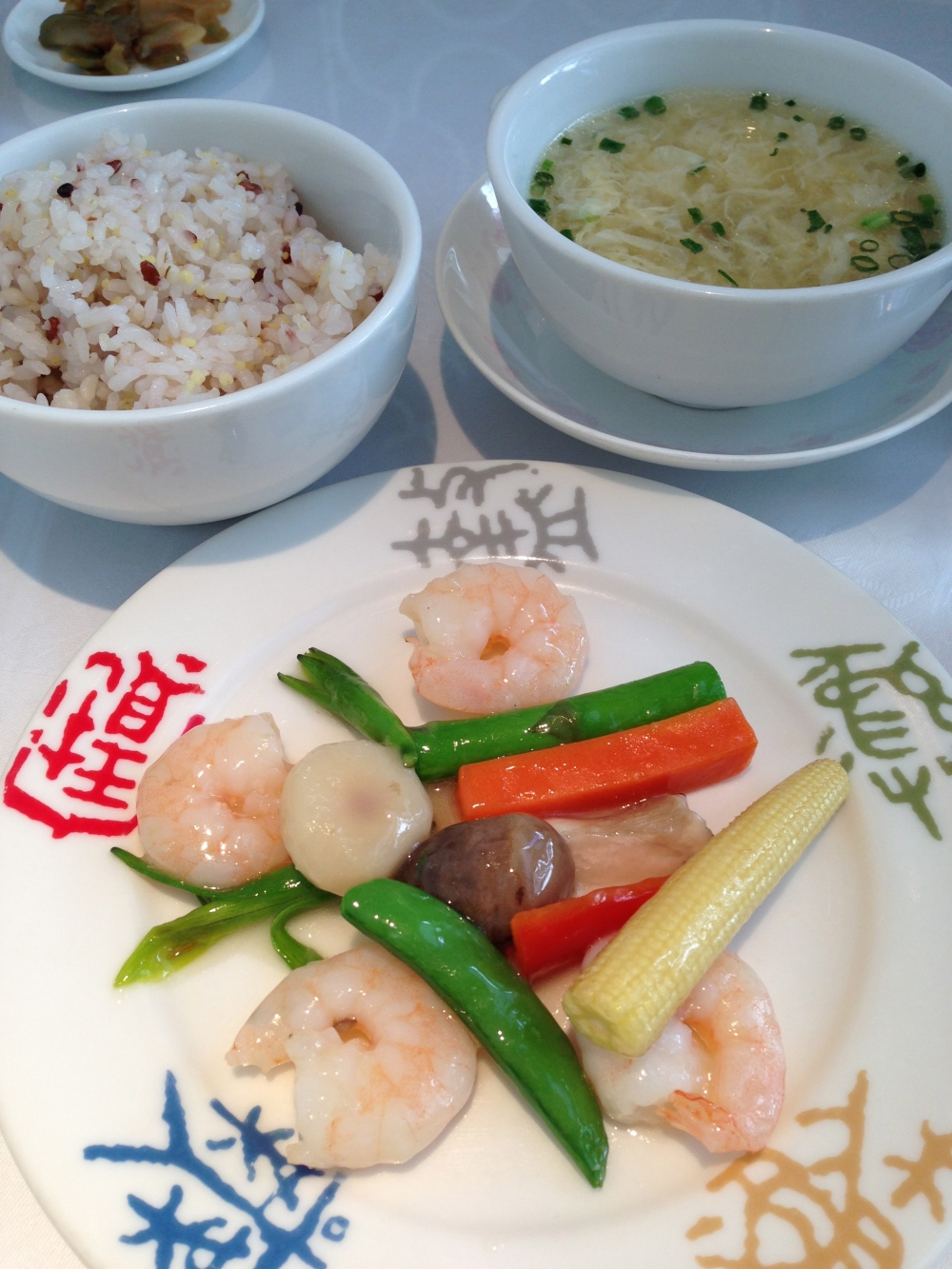 Shrimp stir fried accompanied by a soup and brown rice