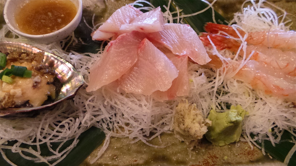 A mixed platter of sashimi and abalone with butter sauce.